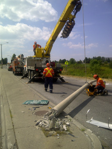 crews replacing a street light pole severed by a motor vehicle accident